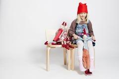 Chica joven que juega con las mu?ecas del duende de la Navidad del juguete Fotos de archivo