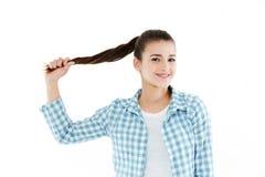 Chica joven que juega con su pelo Fotografía de archivo