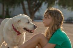 Chica joven que juega con un perro Imagen de archivo