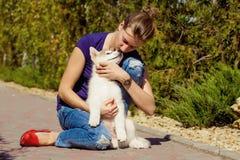 Chica joven que juega con un perro Imagen de archivo libre de regalías