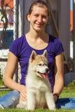 Chica joven que juega con un perro Fotos de archivo
