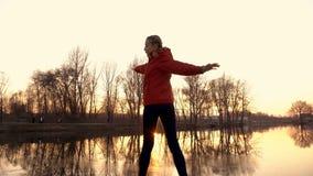 Chica joven que juega deportes en el parque de la ciudad en la puesta del sol Ella hace ejercicios gimnásticos y estirar en el ri almacen de metraje de vídeo