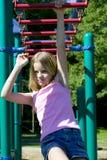 Chica joven que juega en barras de mono en el parque Fotografía de archivo