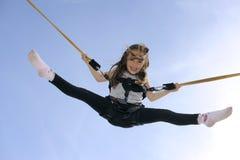 Chica joven que juega en el trampolín del amortiguador auxiliar Fotografía de archivo