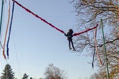 Chica joven que juega en el trampolín del amortiguador auxiliar al aire libre en un parque Fotografía de archivo