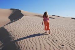 Chica joven que juega en las dunas de arena Foto de archivo libre de regalías