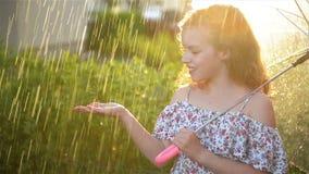 Chica joven que juega en lluvia con el paraguas Ni?o de Cutie que tiene aire libre de la diversi?n almacen de metraje de vídeo