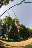 Chica joven que juega en un oscilación fijado en el parque Foto de archivo libre de regalías