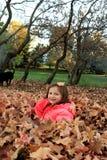 Chica joven que juega en una pila de hojas Imagen de archivo libre de regalías