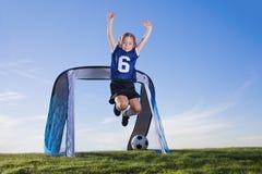 Chica joven que juega a fútbol y que anota meta Foto de archivo libre de regalías