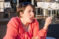 Chica joven que lame a Straw From Her Coffee Cup y que goza de Sunny Day Outside hermoso foto de archivo libre de regalías