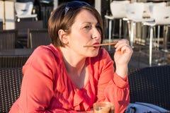 Chica joven que lame a Straw From Her Coffee Cup y que goza de Sunny Day Outside hermoso imágenes de archivo libres de regalías