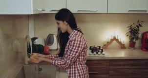 Chica joven que lava las legumbres en la cocina ella está sonriendo 4K almacen de metraje de vídeo