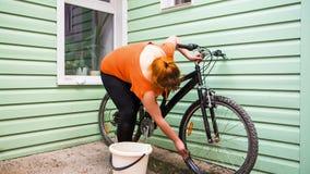 Chica joven que lava las ruedas de bicicleta almacen de metraje de vídeo