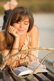 Chica joven que lee la biblia en un banco de parque Fotografía de archivo libre de regalías