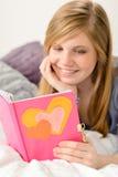 Chica joven que lee su diario de memorias Imagen de archivo libre de regalías