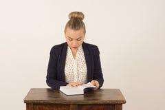 Chica joven que lee un libro Imagenes de archivo