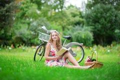 Chica joven que lee un libro en el campo Imagen de archivo libre de regalías