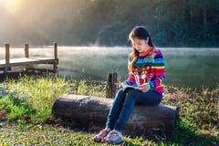 Chica joven que lee un libro en el parque Foto de archivo