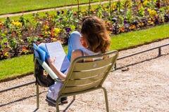 Chica joven que lee un libro en el parque Imagen de archivo libre de regalías