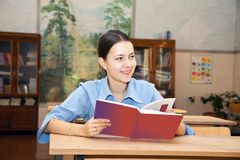 Chica joven que lee un libro en la biblioteca Foto de archivo