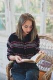 Chica joven que lee un libro en una silla de mimbre Fotografía de archivo libre de regalías