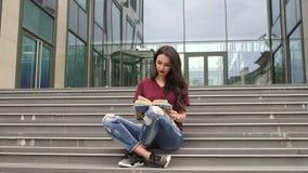 Chica joven que lee un libro que se sienta en las escaleras almacen de video