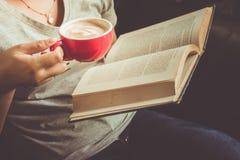 Chica joven que lee un libro y que bebe el café Imagen de archivo