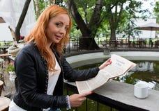 Chica joven que lee un periódico en cafetería fotografía de archivo