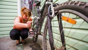 Chica joven que limpia su bicicleta con el cepillo y almacen de video