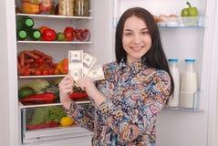 Chica joven que lleva a cabo dólares en el fondo del refrigerador Fotografía de archivo