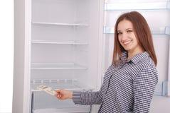 Chica joven que lleva a cabo dólares en el fondo del refrigerador Fotos de archivo libres de regalías