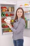 Chica joven que lleva a cabo dólares en el fondo del refrigerador Foto de archivo libre de regalías