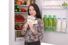 Chica joven que lleva a cabo dólares en el fondo del refrigerador Imagen de archivo