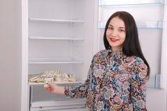 Chica joven que lleva a cabo dólares en el fondo del refrigerador Fotos de archivo