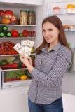 Chica joven que lleva a cabo dólares en el fondo del refrigerador Fotografía de archivo libre de regalías
