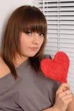 Chica joven que lleva a cabo el corazón en las manos Fotos de archivo libres de regalías