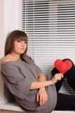 Chica joven que lleva a cabo el corazón en las manos Fotografía de archivo libre de regalías