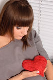 Chica joven que lleva a cabo el corazón en las manos Imagen de archivo libre de regalías