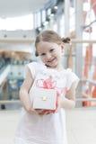 Chica joven que lleva a cabo el presente envuelto en arco rojo grande Foto de archivo libre de regalías