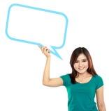 Chica joven que lleva a cabo la burbuja en blanco del texto en espec. Fotografía de archivo libre de regalías