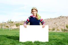 Chica joven que lleva a cabo la muestra en blanco Fotos de archivo