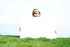 Chica joven que lleva a cabo la muestra en blanco Foto de archivo libre de regalías