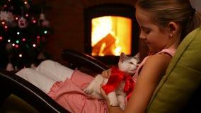 Chica joven que lleva a cabo su regalo de Navidad por el fuego - acariciando un rescate adoptó el gatito metrajes