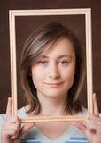 Chica joven que lleva a cabo un marco Fotos de archivo