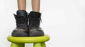 Chica joven que lleva las botas de su padre. Imagen de archivo libre de regalías