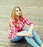 Chica joven que lleva una reclinación que se sienta de la camisa rosada Fotografía de archivo