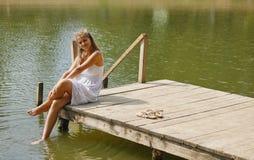Chica joven que lleva una sentada blanca por el río por tarde del verano Fotos de archivo