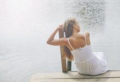 Chica joven que lleva una sentada blanca por el río por tarde del verano Fotos de archivo libres de regalías