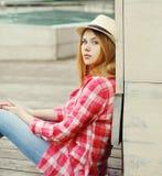 Chica joven que lleva una sentada rosada de la camisa y del sombrero del verano Fotografía de archivo